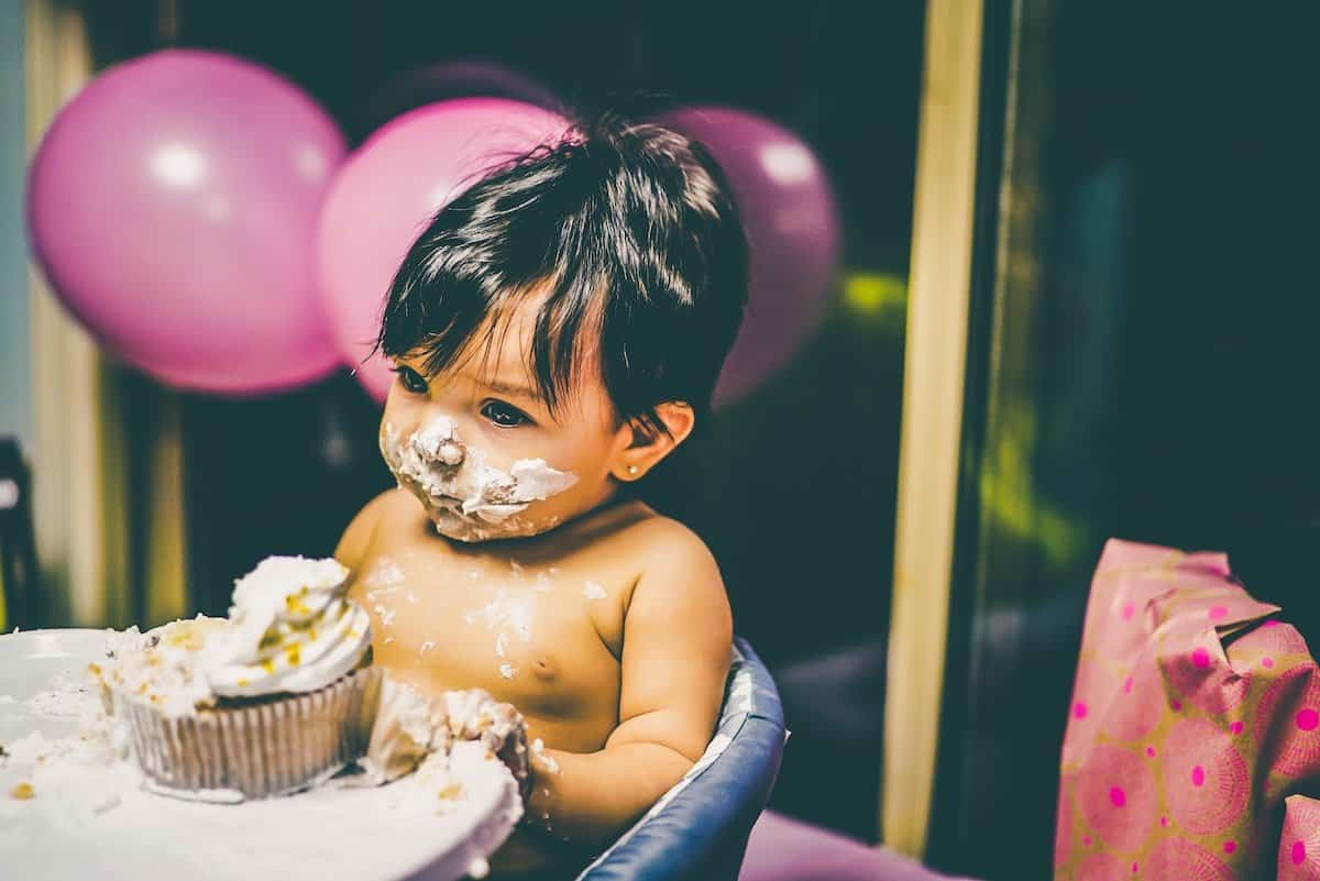 baby with black hair sitting in front of a cupcake with pink balloons in background