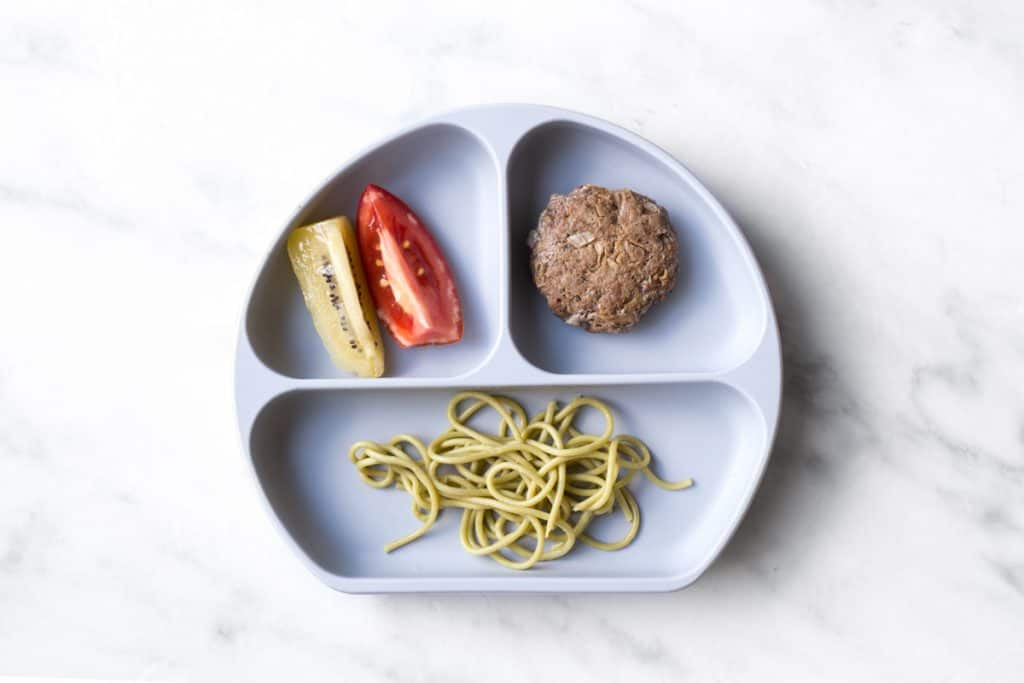 A divided baby plate with spaghetti noodles in one section, a baby beef meatball in another, and a slices of kiwi and a slice of tomato in the last section.