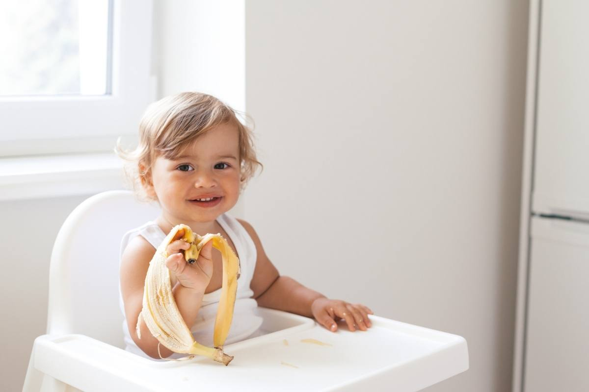 Young toddler girl sitting in high chair holding a banana peel