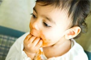 baby stuffing food in mouth